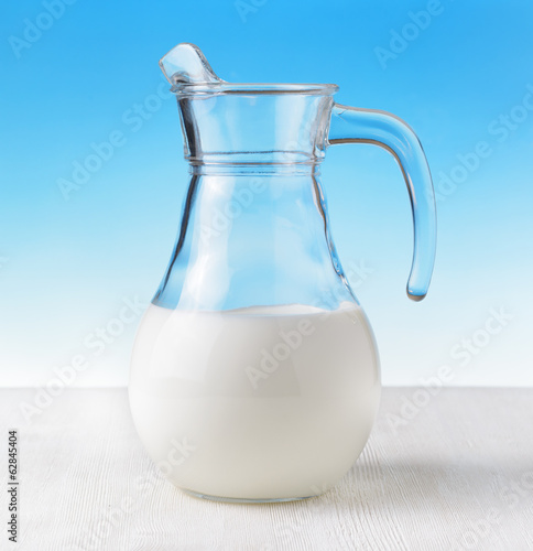 Jug of milk on sky background. Half full pitcher