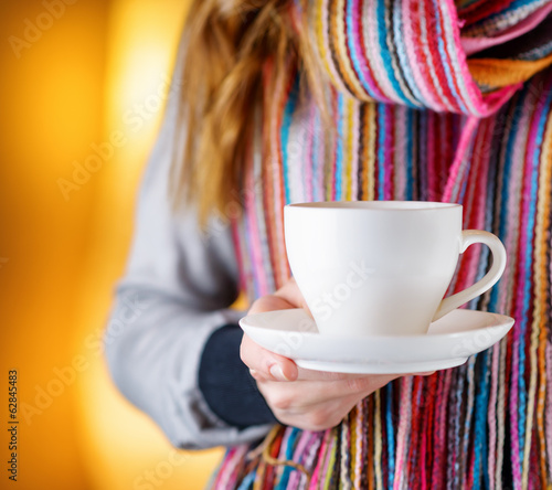 Young woman holding a cup of coffee in cafe