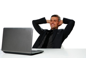 Relaxed happy businessman sitting at the table