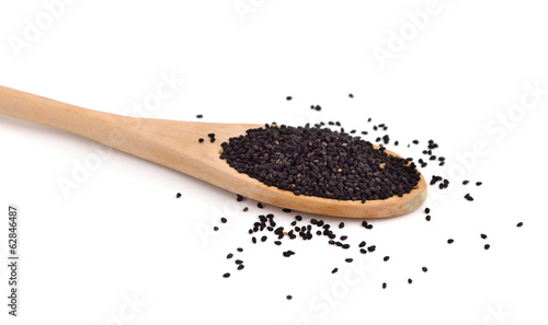 Nigella seeds in a wooden spoon.