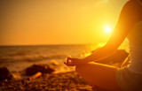 Fototapety hand of  woman meditating in a yoga pose on beach at sunset