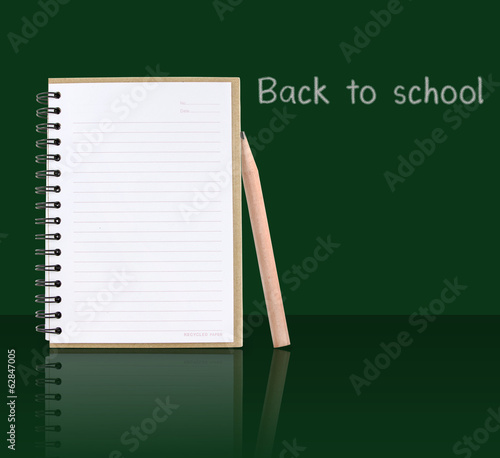 Opened notebook beside by pencil with shadow effect on green