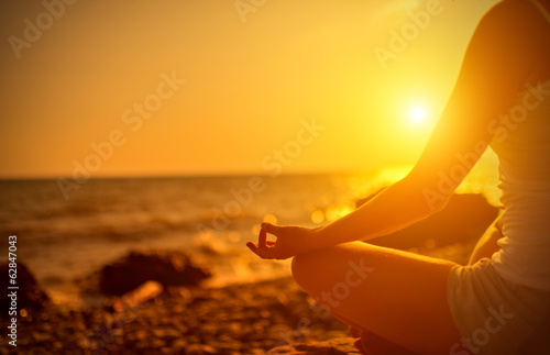 Poster hand of  woman meditating in a yoga pose on beach at sunset