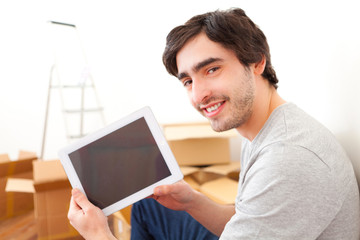 Handsome young man in his new flat using tablet