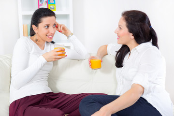 Two happy young female friends with juice conversing