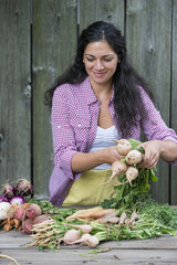 A woman sorting freshly picked vegetables on a table.