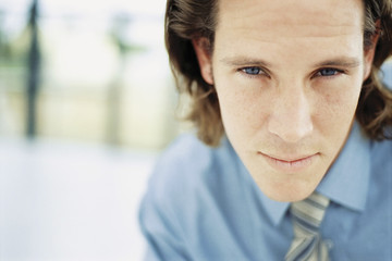 A young man with curly brown hair wearing a blue shirt and tie.