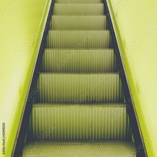 A flight of steps, an escalator with a yellow painted border stripe on each side.
