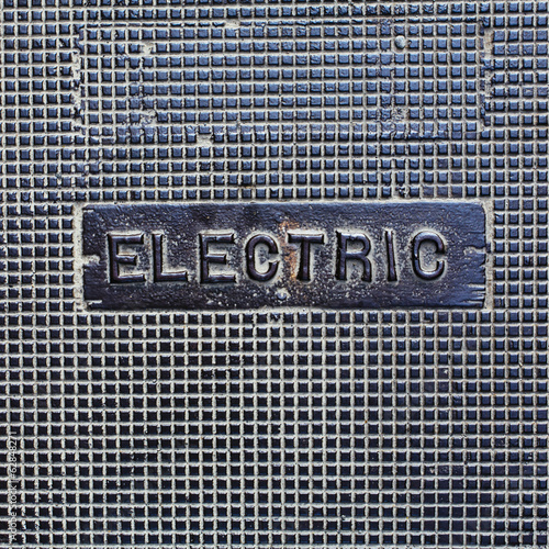 A utility cover made of metal, with the word Electric.