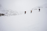 Three skiers ascending a ridge in mist and cloud conditions on the Wapta Traverse, a mountain hut to hut ski tour in Alberta, Canada.