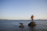 A sea kayaker stands on a rock in the water at sunset off the coast of Seattle in the Puget Sound, Washington, USA.