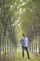A man standing in an avenue of trees, looking upwards.