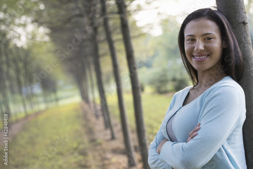 A woman with arms folded, leaning against a tree.