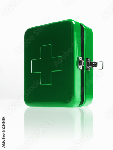 Green metal first aid box with fastener and large cross on the top.