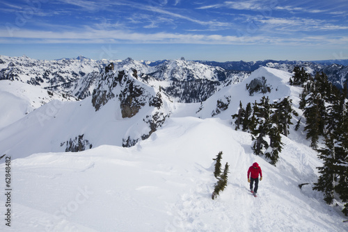 A climber in a red jacket on the summit of Snoqualmie Peak in the Cascades range of mountains in Washington state, USA.