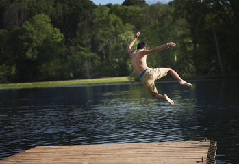 A boy taking a running jump into a calm pool of water, from a wooden jetty.