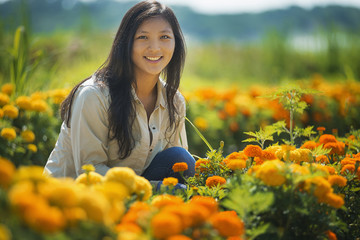 A young woman in a garden surrounding by flowers.