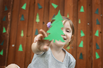 A child playing with a green tree mobile.