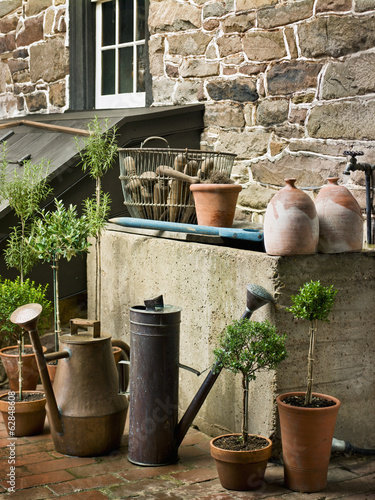 A collection of old watering cans, and clay pots for plants, outside a house.