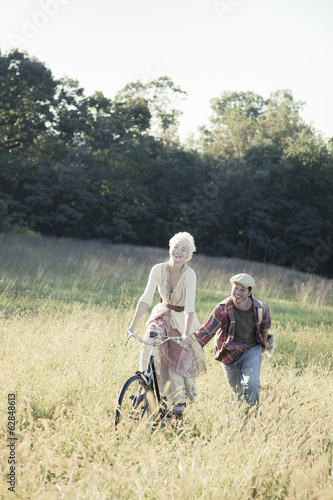 A girl on a bicycle being pushed through the long grass by a young man.