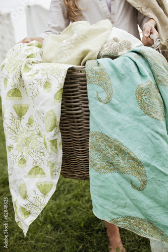 A basket overflowing with household linens. Washing basket.