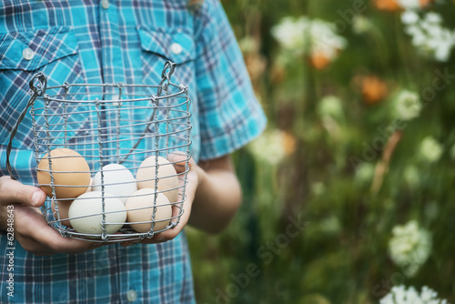 A person holding a basket of freshly laid hen's eggs, of varying colours.