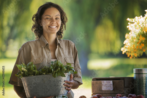A young woman with a large bucket of salad vegetables leaves freshly picked.