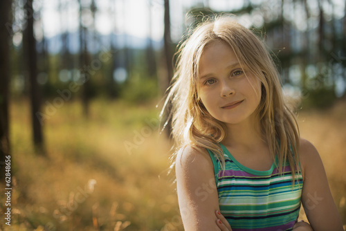 A child with long blonde hair in woodland by a lake.