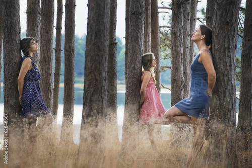 A group of people communing with nature, and leaning against tall straight trees in woodland.