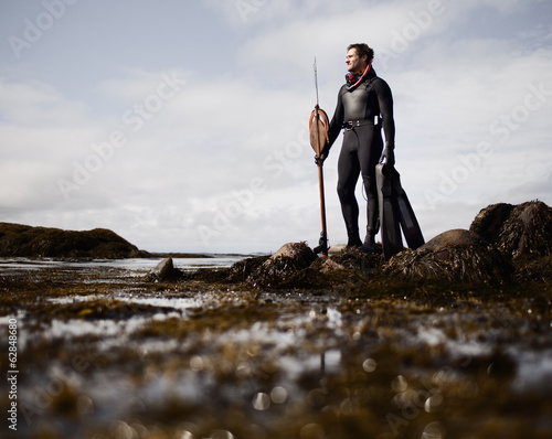 A man in a wetsuit, standing on the shore with a large spear fishing harpoon.