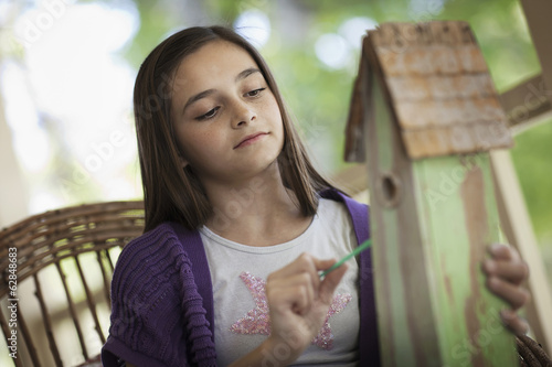 A child examining a bug box on a porch.