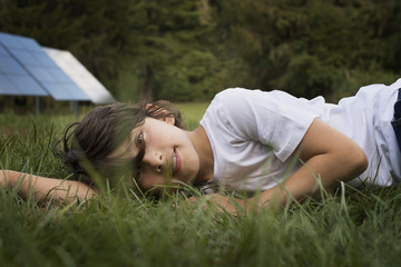 A boy lying in the grass, beside a solar panel.