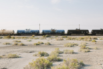 A goods train on the train track running through the desert. Freight wagons.