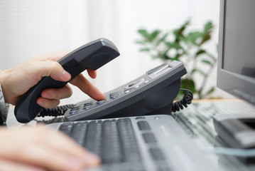 businessman is dialing a phone number in office