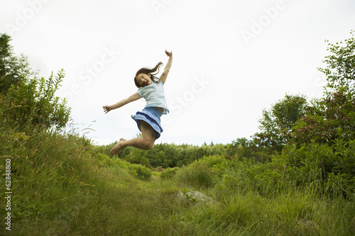 A young girl, leaping for joy, kicking up her heels in the air.