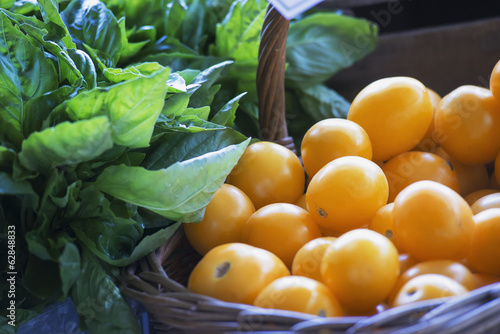 Organic yellow tomatoes and basil herb leaves on a market stall.