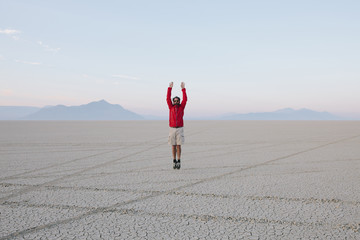 A man jumping in the air on the flat desert or playa or Black Rock Desert, Nevada.