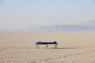 Sleeping bag on cot in vast, barren desert, dawn