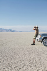 A man leaning against a truck, looking through binoculars.