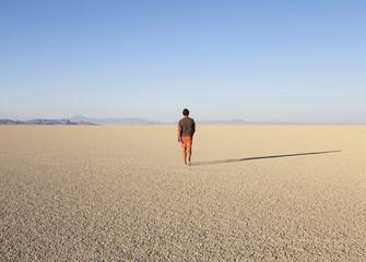 Man walking across a flat desert landscape