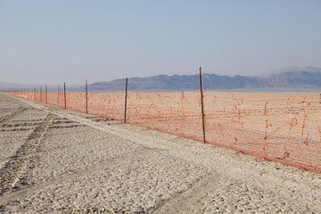 Fence barricade extending across the flat landscape, Black Rock Desert, Nevada, USA
