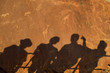 The shadows of tourists at a viewing point, on the surface of the rock at  Twyfelfontein World Heritage Site at Uibasen Conservancy, Damaraland, Namibia.