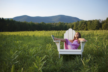 A young girl sitting in a traditional wooden Adirondack style chair in a field at evening light.