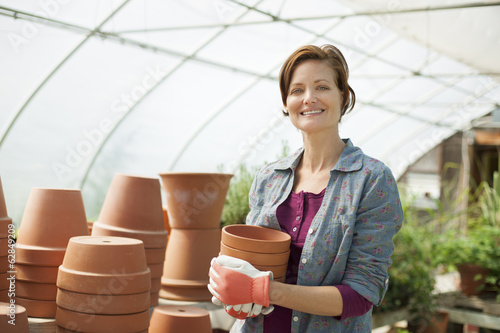 A woman wearing work gloves carrying terracotta plant pots in a large greenhouse on an organic farm.