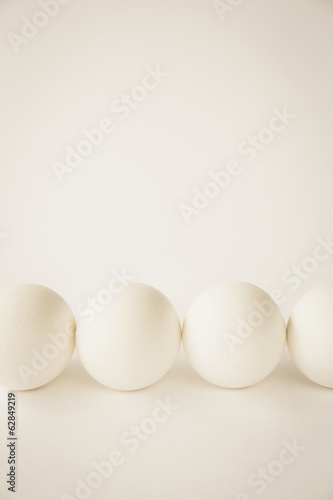 End-on view of free range, organic eggs with white shells arranged in a row, on a cream coloured background.