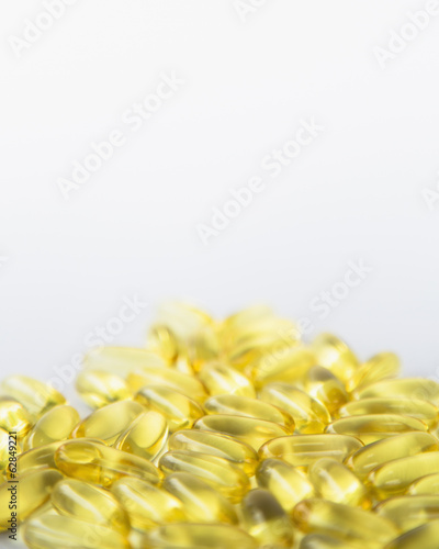Fish oil providing Omega-3, in softgel supplement capsules. An essential fatty acid and health supplement product.
