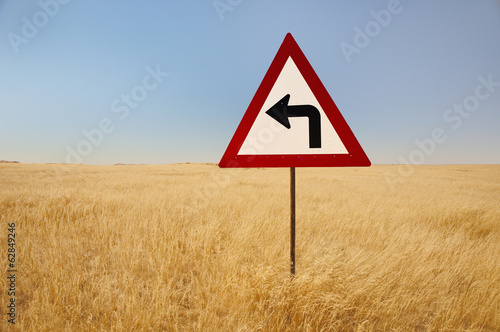 A turn left traffic sign, in the middle of tall grasses, in the savanna of  Namibia.