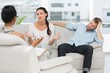 Angry couple sitting on couch talking to therapist