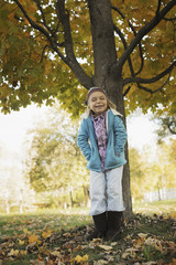 A young girl standing under a tree, on a farm. Autumn foliage.