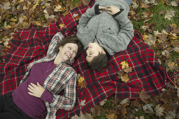 Two people, a woman and a child, lying on a red tartan picnic blanket, looking upwards.
